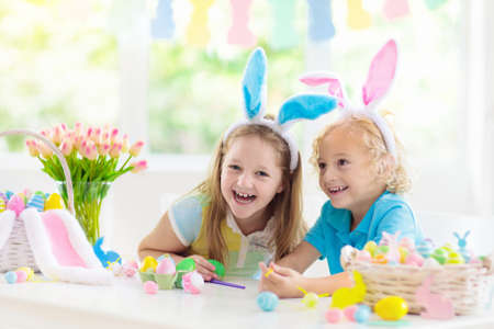 Kids dyeing Easter eggs. Children in bunny ears dye colorful egg for Easter hunt. Home decoration with flowers, basket and rabbit for spring holiday celebration. Little boy and girl decorate home.