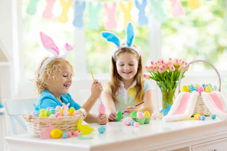 Kids dyeing Easter eggs. Children in bunny ears dye colorful egg for Easter hunt. Home decoration with flowers, basket and rabbit for spring holiday celebration. Little boy and girl decorate home. 版權商用圖片 - 118774845