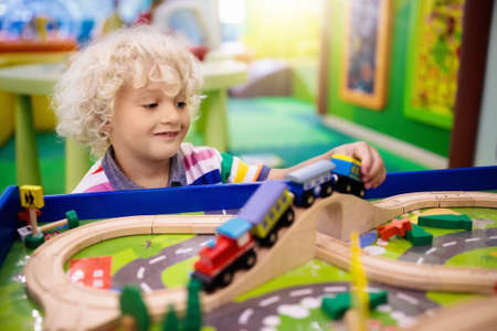 Kids play toy railroad. Little blond curly boy with wooden trains in indoor playground or amusement center. Child with car and train toys at home or daycare. Kindergarten or preschool play room. Imagens