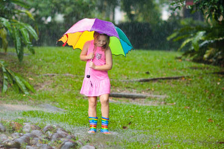 Kid playing out in the rain. Children with umbrella and rain boots play outdoors in heavy rain. Little girl jumping in muddy puddle. Kids fun by rainy autumn weather. Child running in tropical storm. Foto de archivo - 118775227