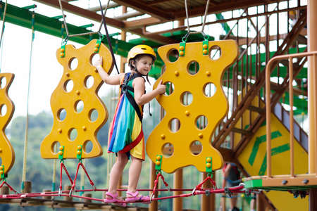 Child in forest adventure park. Kids climb on high rope trail. Agility and climbing outdoor amusement center for children. Little girl playing outdoors. School yard playground with rope way. Banque d'images - 118775233