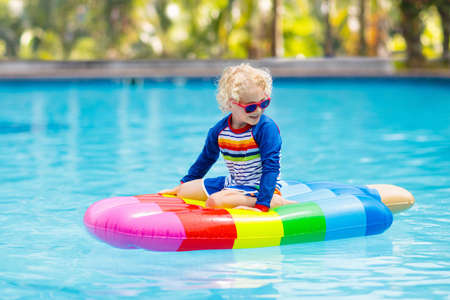 Happy child on inflatable ice cream float in outdoor swimming pool of tropical resort. Summer vacation with kids. Swim aids and wear for children. Water toys. Little boy floating on colorful raft. Reklamní fotografie