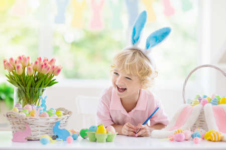 Kids dyeing Easter eggs. Children in bunny ears dye colorful egg for Easter hunt. Home decoration with flowers, basket and rabbit for spring holiday celebration. Little baby boy decorating home.