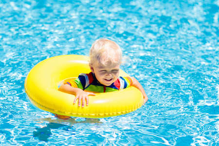 Child in swimming pool floating on toy ring. Kids swim. Colorful yellow float for young kids. Little boy having fun on family summer vacation in tropical resort. Beach and water toys. Sun protection.