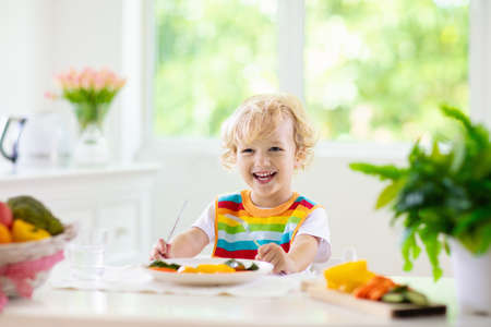 Child eating vegetables sitting in white high chair. Solid food for baby. Little boy eating healthy vegetable lunch of steam cooked carrots. Nutrition for toddler and preschooler. Kids eat fruit. Banque d'images - 118775918