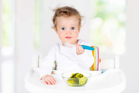Baby eating vegetables sitting in white high chair. Solid food for infant. Little girl eating healthy vegetable lunch of steam cooked broccoli. Nutrition for toddler and preschooler. Kids eat fruit. Banque d'images