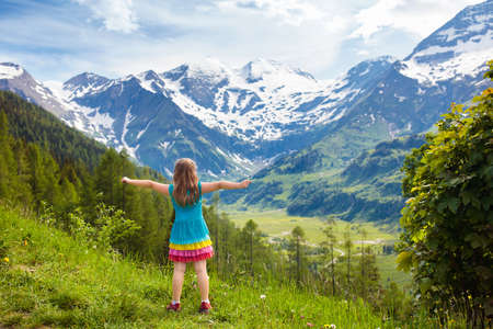 Children hiking in Alps mountains. Kids look at the snow covered mountain in Austria. Spring family vacation. Little girl on hike trail in blooming alpine meadow. Outdoor fun and healthy activity. 写真素材