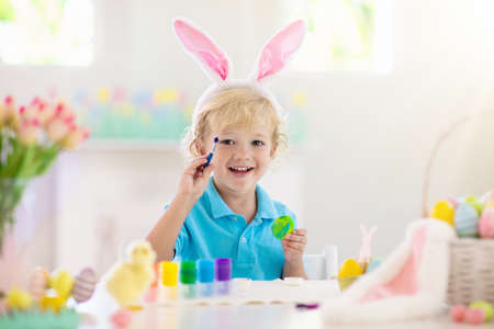 Kids dyeing Easter eggs. Children in bunny ears dye colorful egg for Easter hunt. Home decoration with flowers, basket and rabbit for spring holiday celebration. Little baby boy decorating home. 版權商用圖片 - 118775942