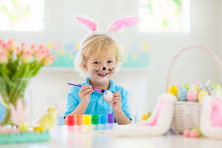 Kids dyeing Easter eggs. Children in bunny ears dye colorful egg for Easter hunt. Home decoration with flowers, basket and rabbit for spring holiday celebration. Little baby boy decorating home. 版權商用圖片 - 119039901