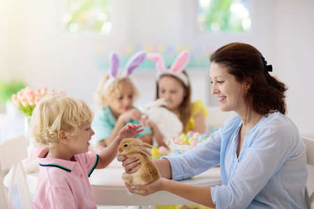 Mother and kids with pet rabbit color Easter eggs. Mom, little girl and boy with bunny ears dying and painting for Easter egg hunt in white sunny room. Family celebration and home decoration in spring