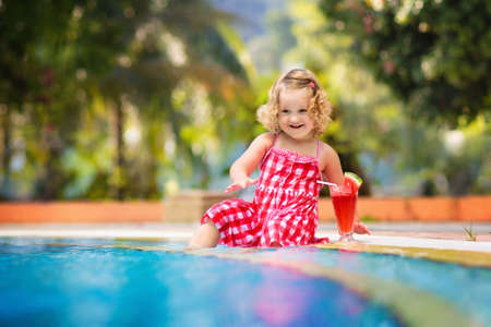 Beautiful little girl, cute toddler with curly hair wearing a red summer dress, sitting at a swimming pool drinking water melon juice with fresh fruit having fun on family vacation in tropical resort
