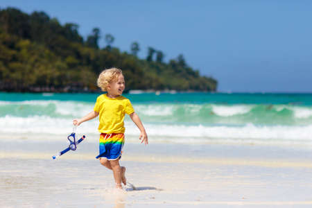 Child snorkeling on tropical beach. Kids snorkel in ocean on family summer vacation on exotic island. Little boy playing with water and sand at sea shore. Toddler running in waves. Beach fun for kid. 写真素材