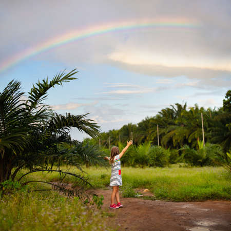 Child watching rainbow on tropical island with palm trees. Kids play outdoors by rain. Little girl looking at rainbow after summer shower. Outdoor fun by rainy weather for children. Travel with kid. 写真素材