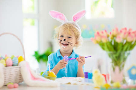 Kids dyeing Easter eggs. Children in bunny ears dye colorful egg for Easter hunt. Home decoration with flowers, basket and rabbit for spring holiday celebration. Little baby boy decorating home. Stock Photo - 119040098