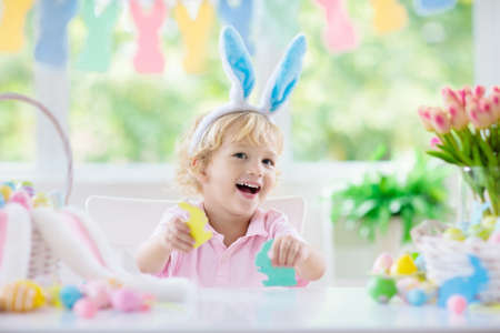 Kids dyeing Easter eggs. Children in bunny ears dye colorful egg for Easter hunt. Home decoration with flowers, basket and rabbit for spring holiday celebration. Little baby boy decorating home. 版權商用圖片 - 119581158
