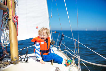 Kids sail on yacht in sea. Child sailing on boat. Little boy in safe life jackets travel on ocean ship. Children enjoy yachting cruise. Summer vacation for family. Young sailor on sailboat front deck.