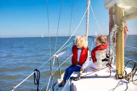 Kids sail on yacht in sea. Child sailing on boat. Little boy and girl in safe life jackets travel on ocean ship. Children enjoy yachting cruise. Summer vacation for family. Young sailors on sailboat. Stok Fotoğraf - 119583288