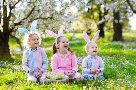 Kids with bunny ears on Easter egg hunt in blooming cherry blossom garden. Little boy and girl with spring flowers and eggs basket in fruit orchard. Children search for colorful eggs, candy and sweets Stock Photo - 119583289