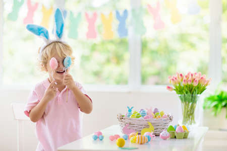 Kids dyeing Easter eggs. Children in bunny ears dye colorful egg for Easter hunt. Home decoration with flowers, basket and rabbit for spring holiday celebration. Little baby boy decorating home. 版權商用圖片 - 119583376