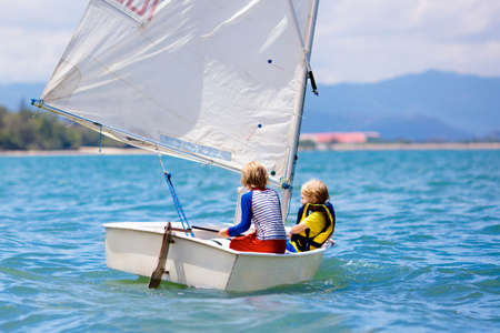 Child sailing. Kid learning to sail on sea yacht. Healthy water sport for school kids. Yachting class for young sailor. Children on boat. Family summer vacation on tropical island. Beach activity. Reklamní fotografie