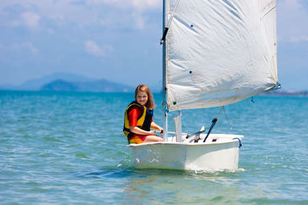 Child sailing. Kid learning to sail on sea yacht. Healthy water sport for school kids. Yachting class for young sailor. Children on boat. Family summer vacation on tropical island. Beach activity. 版權商用圖片