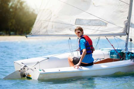 Child sailing. Kid learning to sail on sea yacht. Healthy water sport for school kids. Yachting class for young sailor. Children on boat. Family summer vacation on tropical island. Beach activity. Banco de Imagens