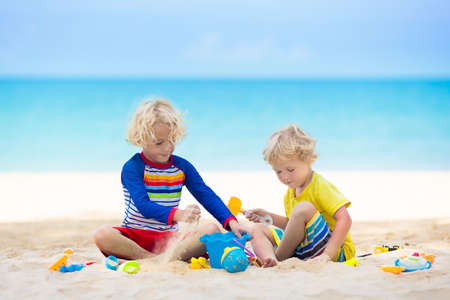 Kids playing on tropical beach. Children play at sea on summer family vacation. Sand and water toys, sun protection for young child. Little boy digging sand, building castle at ocean shore.