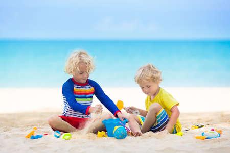 Niños jugando en la playa tropical. Los niños juegan en el mar en vacaciones familiares de verano. Juguetes para la arena y el agua, protección solar para niños pequeños. Niño cavando arena, construyendo un castillo en la orilla del mar.