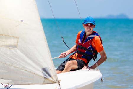 Młody człowiek żeglarstwo. Nastolatek chłopiec na morskim jachcie. Zdrowy sport wodny. Klasa żeglarska dla nastoletniego żeglarza. Wakacje nad oceanem na łodzi. Regaty na tropikalnej wyspie. Aktywność na plaży i na żaglach.