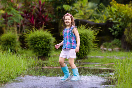 Kid playing out in the rain. Children with umbrella and rain boots play outdoors in heavy rain. Little boy jumping in muddy puddle. Kids fun by rainy autumn weather. Child running in tropical storm. Stock Photo