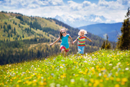 Children hiking in Alps mountains. Kids run at snow covered mountain in Austria. Spring family vacation. Little boy and girl on hike trail in blooming alpine meadow. Outdoor fun and healthy activity. Standard-Bild - 121570445
