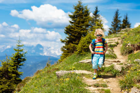 Children hiking in Alps mountains. Kids look at snow covered mountain in Austria. Spring family vacation. Little boy on hike trail in blooming alpine meadow. Outdoor fun and healthy activity. 免版税图像
