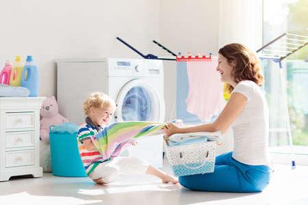Mutter und Kinder in der Waschküche mit Waschmaschine oder Wäschetrockner. Familienarbeiten. Moderne Haushaltsgeräte und Waschmittel im weißen sonnigen Haus. Waschen Sie gewaschene Kleidung auf dem Wäscheständer. Standard-Bild