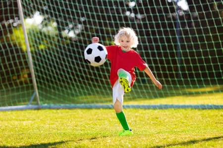 Kids play football on outdoor field. Portugal team fans. Children score a goal at soccer game. Boy in Portuguese jersey and cleats kicking ball. Football club pitch. Sports training for young player. Stockfoto