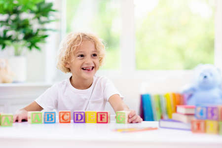 Child learning letters and numbers. Kid with colorful wooden abc blocks. Little boy spelling words with educational block toys. Kids doing school homework at white desk. Bedroom for preschool children Banco de Imagens