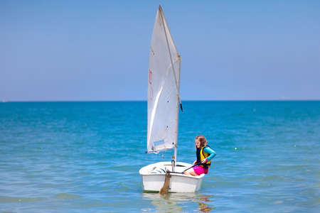 Child sailing. Kid learning to sail on sea yacht. Healthy water sport for school kids. Yachting class for young sailor. Children on boat. Family summer vacation on tropical island. Beach activity. Stock fotó