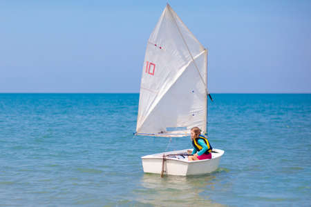 Child sailing. Kid learning to sail on sea yacht. Healthy water sport for school kids. Yachting class for young sailor. Children on boat. Family summer vacation on tropical island. Beach activity. 스톡 콘텐츠