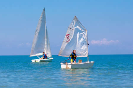 Child sailing. Kid learning to sail on sea yacht. Healthy water sport for school kids. Yachting class for young sailor. Children on boat. Family summer vacation on tropical island. Beach activity. Stock Photo