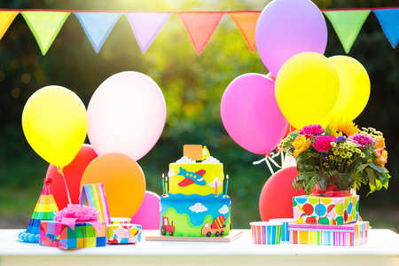 Kids birthday party decoration. Colorful cake with candles. Car and transportation theme boys party. Decorated table for child birthday celebration. Rainbow cake for little boy. Balloons and banners.