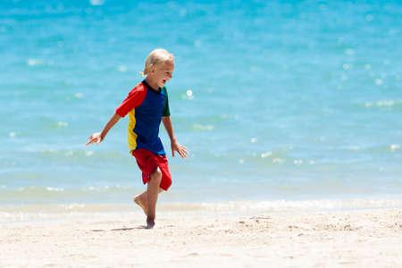 Kinder spielen am tropischen Strand. Kinder schwimmen und spielen im Sommer im Familienurlaub auf See. Sand- und Wasserspaß, Sonnenschutz für Kleinkinder. Kleiner Junge und Mädchen, die am Ozeanufer laufen und springen. Standard-Bild
