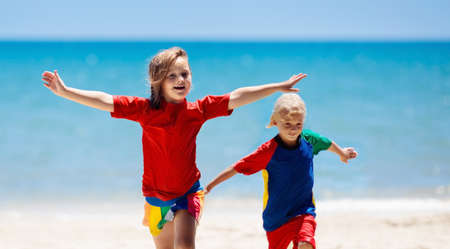 Kids playing on tropical beach. Children swim and play at sea on summer family vacation. Sand and water fun, sun protection for young child. Little boy and girl running and jumping at ocean shore. 写真素材