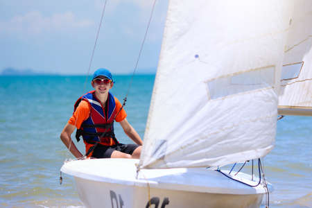Young man sailing. Teenager boy on sea yacht. Healthy water sport. Yachting class for teen age sailor. Ocean vacation on boat. Regatta on tropical island. Beach and sail activity. Imagens - 121571100