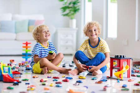 Kinder spielen mit Spielzeugautos im Reinraum. Kleiner Junge, der mit Auto- und LKW-Spielzeug spielt. Fahrzeug- und Transportspiel für Kinder. Kind mit Parkgarage. Kind hat Spaß zu Hause oder in der Kindertagesstätte.