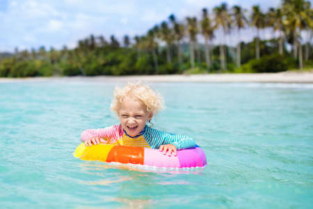 Child with inflatable ring on beautiful beach. Little boy swimming in exotic sea. Ocean vacation with kid. Children play on summer beach. Water fun. Kids swim. Family holiday on tropical island. 写真素材