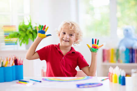 Kids paint. Child painting in white sunny study room. Little boy drawing rainbow. School kid doing art homework. Arts and crafts for kids. Paint on children hands. Creative little artist at work.