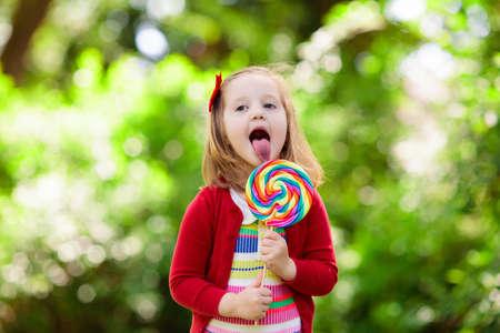 Nettes kleines Mädchen mit großem buntem Lutscher. Kind, das süßen Schokoriegel isst. Süßigkeiten für kleine Kinder. Sommerspaß im Freien. Vorschulkind mit Zuckerlutscher. Kinder, die nach der Vorschule einen Snack in einem Park haben.