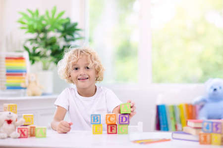 Child learning letters and numbers. Kid with colorful wooden abc blocks. Little boy spelling words with educational block toys. Kids doing school homework at white desk. Bedroom for preschool children Stock Photo