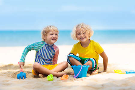Kids playing on tropical beach. Children play at sea on summer family vacation. Sand and water toys, sun protection for young child. Little boy digging sand, building castle at ocean shore. Stockfoto