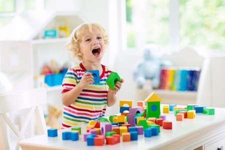 Bambino che gioca con blocchi giocattolo colorati. Ragazzino che costruisce una torre di giocattoli a blocchi. Giocattoli e giochi educativi e creativi per bambini piccoli. Bambino in camera da letto bianca con mattoni arcobaleno. Bambino a casa. Archivio Fotografico