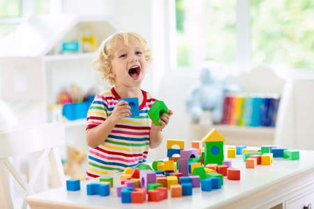 Kid spelen met kleurrijke blokken. Kleine jongen die toren van blokspeelgoed bouwt. Educatief en creatief speelgoed en spelletjes voor jonge kinderen. Baby in witte slaapkamer met regenboogbakstenen. Kind aan huis. Stockfoto